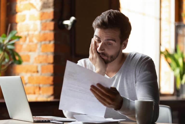 Man Looking At Student Loan Papers