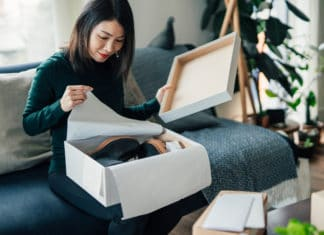 Woman Opening Boot Box Sitting Couch