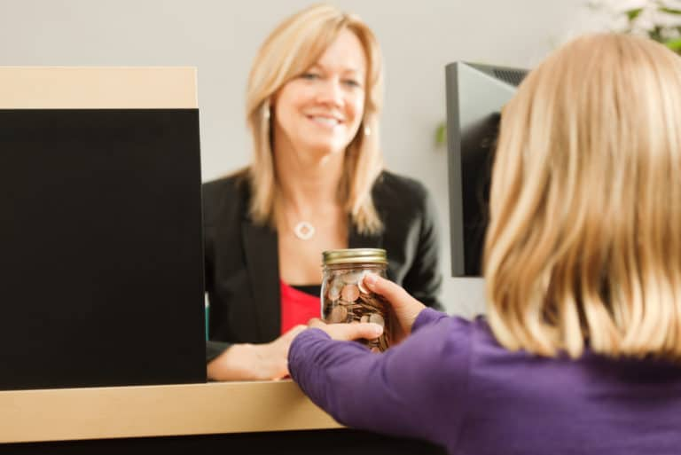 Child Handing Jar Coins Bank Teller