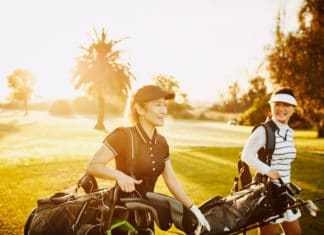 Laughing Woman Walking On Fairway While Playing Golf With Mother