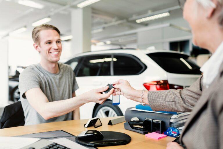 Happy Man Receiving Car Keys Saleswoman Desk