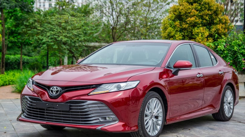 Red Toyota Camry Trees Background