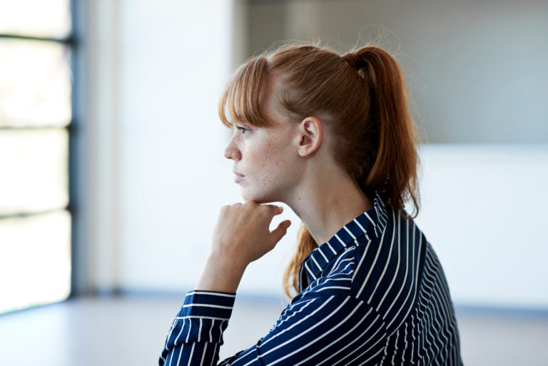 Young Woman Thinking While Outside Window